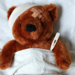 Sick teddy with injury in bed - Stockfoto