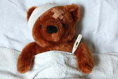 Sick teddy with injury in bed — Stockfoto