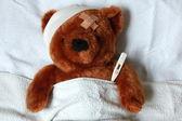 Sjukt teddy med skada i sängen — Stockfoto