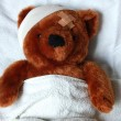 Sick teddy with injury in bed — Stock Photo #3484765