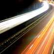 Road with car traffic at night with blurry lights - Stock Photo