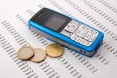 Mobilní telefon přes obchodní graf — Stock fotografie