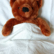 Sick teddy with injury in bed — Stock Photo