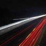bulanık ışıkları ile gece araba trafiği olan yol — Stok fotoğraf