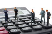 Toy business man on calculator isolated — Stock Photo