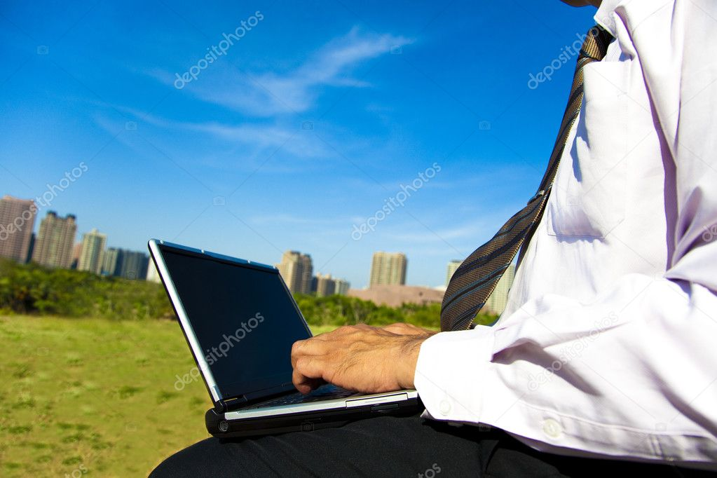 Business man working on a laptop outdoors sitting on a park bench — Stock Photo #3028972