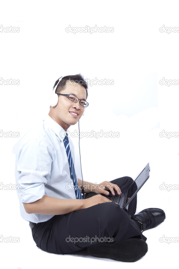Smiling young businessman sitting and using a laptop   Stock Photo #3635525