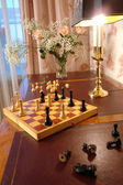 Table with chess, flowers and lamp — Stock Photo