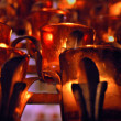 Foto Stock: Church candles in red and yellow transparent chandeliers