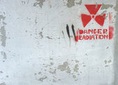White peeling paint on wall with radiation warning — Stock Photo