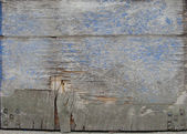 Detail of a heavily worn damaged blue wooden door — Stock Photo