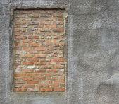 Brick filled window on stucco concrete dirty worn wall — Stock Photo