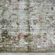 Dirty worn painted white factory brick wall with some moss — Stock Photo