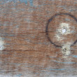Circular burn mark on worn wood with leftovers from paint — Stock Photo #3484927