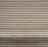 Worn metal garage door gate store roller shutter — Stock Photo