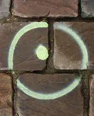Sprayed circle and dot on a semi wet cobble stone pavement — Stock Photo