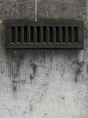 Metal ventilation vent in a worn dirty gray wall — Stock Photo