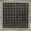 Irregular metal grid from a ventilation shaft in a concrete wall — Stock Photo