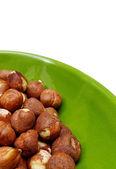 Lískové ořechy v zelené prohlubni nad bílá — Stock fotografie