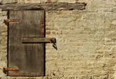Little wooden window with padlock in beige painted brick wall — Stock Photo