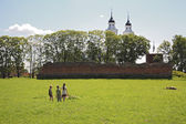 Three children on field by Livonia order castle ruins and church — Stock Photo