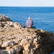 Royalty-Free Stock Photo: Fisherman sitting on the rocks.
