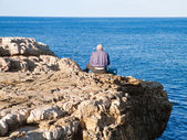 Fisherman sitting on the rocks. — Stock Photo
