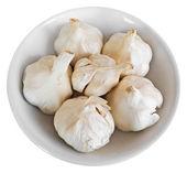 Cloves of garlic on white dish. — Stock Photo