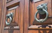 Doorknocker couple on allwood door. — Stock Photo