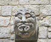Ancient stone face carved on brickwall. — Stock Photo