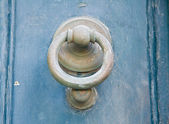 Doorknocker on blue wooden frontdoor. — Stock Photo