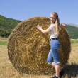 Blonde girl leaning against a rolling haystack. — Stock Photo