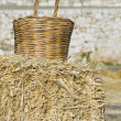 Stockfoto: Wicker basket leaning on haystack bale.