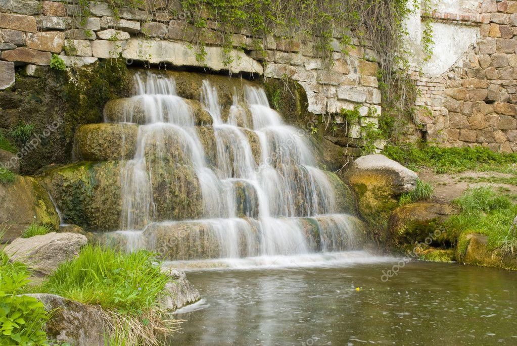 de oude muur en mondt uit in de vijver in het park aan de oevers van ...