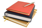 Stack of books with notepad and pen — Stock Photo