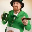 Leprechaun drinking green beer — Stock Photo