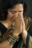 улыбаясь индийская женщина молится — Стоковое фото