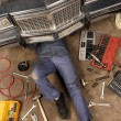 Mechanic under the car - Stock Photo