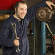 Stock Photo: Crazy mechanic fixing the brakes