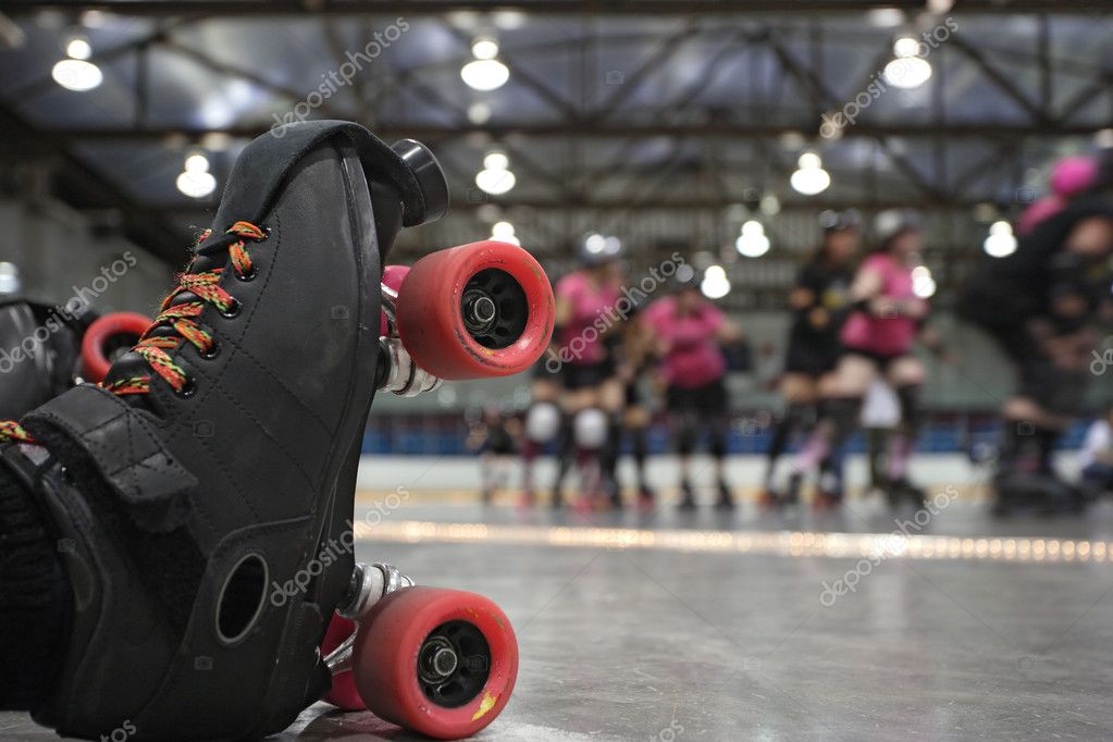 An abstract image of the roller-skates of a fallen skater as her teammates in the background continue to skate around the track of the roller derby. — Stock Photo #3490820