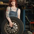 Female mechanic changing tires — Stock fotografie