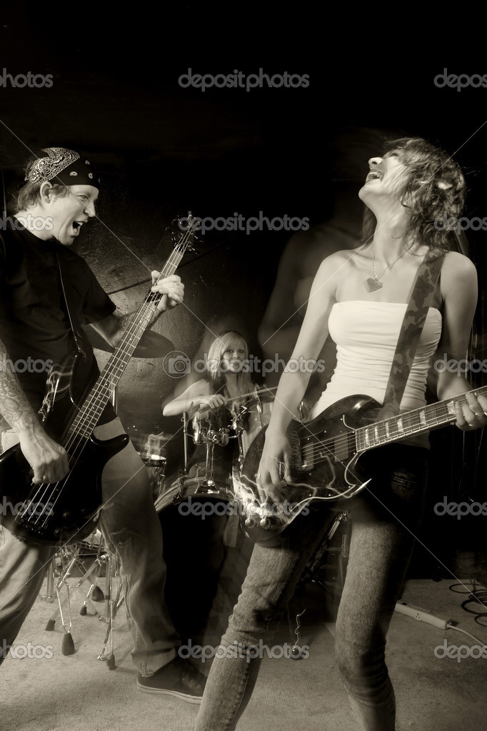 Band playing on a stage. Male bassist with female guitarist and drummer. Shot with strobes and slow shutter speed to create lighting atmosphere and blur effects — Stock Photo #3657461