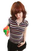 Pretty girl pointing squirt gun — Stock Photo
