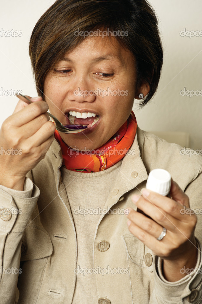 An Asian female in her early 40's taking a spoonful of cough medicine. — Stock Photo #3909273