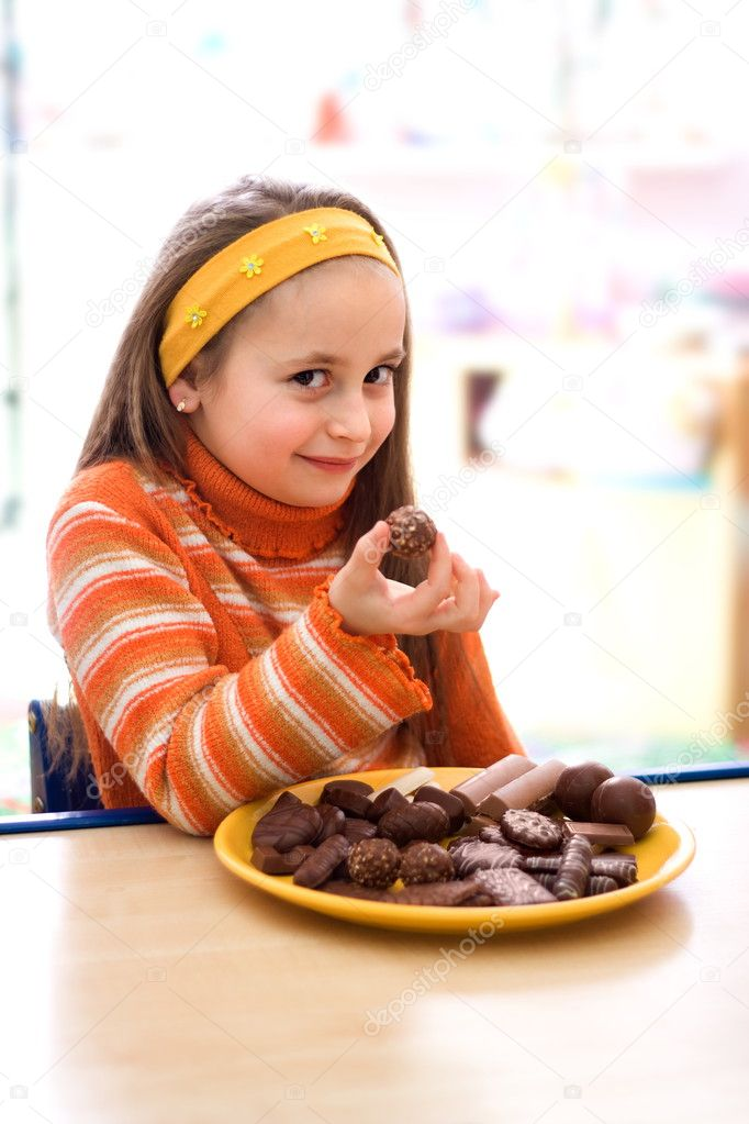 Pretty young girl taking a peace of chocolate from tray — Stock Photo #3054417