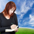 Cute redhead writing in her notebook or diary — Stock Photo