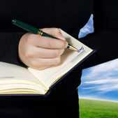 Hand writing down a note saying sold — Stock Photo