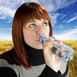 Redhead girl drinking water — Stock Photo
