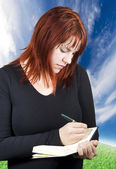 Cute redhead writing in her notebook or diary — Stockfoto