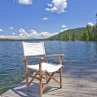 A chair on the dock of a beautiful lake - Stock Photo